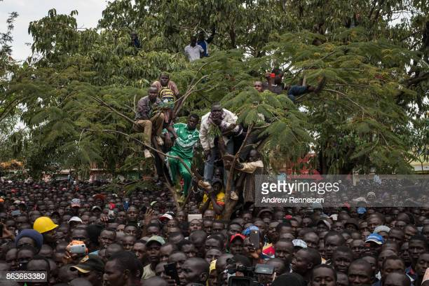 Supporters listen to opposition candidate Raila Odinga as he speaks to a crowd gathered at a funeral service for three men killed by the police...