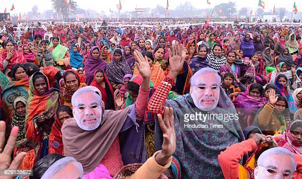 BJP supporters listen to Prime Minister Narendra Modi as he delivers a speech through mobile phone during a Parivartan rally on December 11 2016 in...