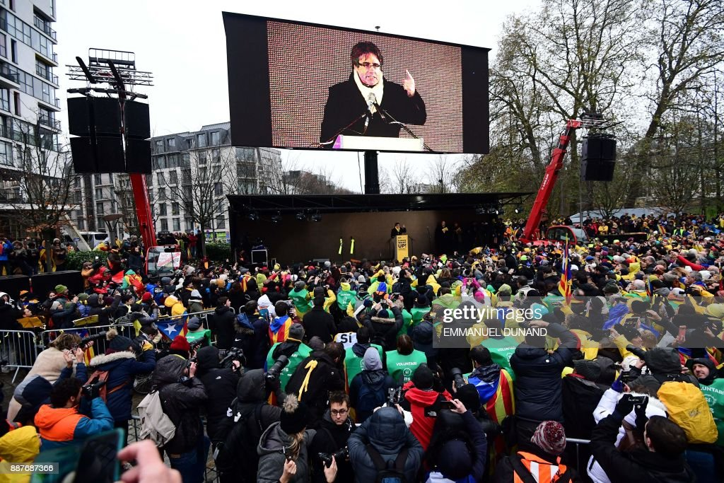 TOPSHOT - Supporters listen to the speech of Catalonia's deposed regional president Carles Puigdemont during a pro-independence demonstration on December 7, 2017 in Brussels during a pro-independence demonstration on December 7, 2017 in Brussels. A sea of around 45,000 pro-Catalonia protesters demonstrated in Brussels on December 7 to show support for the region's deposed president and urge the EU to support its drive for independence from Spain. / AFP PHOTO / Emmanuel DUNAND