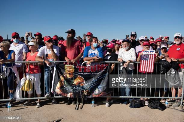 Supporters listen to US President Donald Trump speaking during a Make America Great Again rally at Phoenix Goodyear Airport October 28 in Goodyear,...