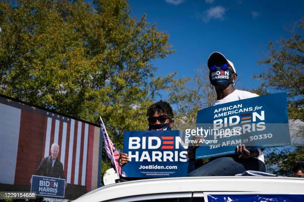 Supporters listen while sitting atop their car as Democratic presidential nominee Joe Biden speaks during a drive-in campaign rally at Riverside High...