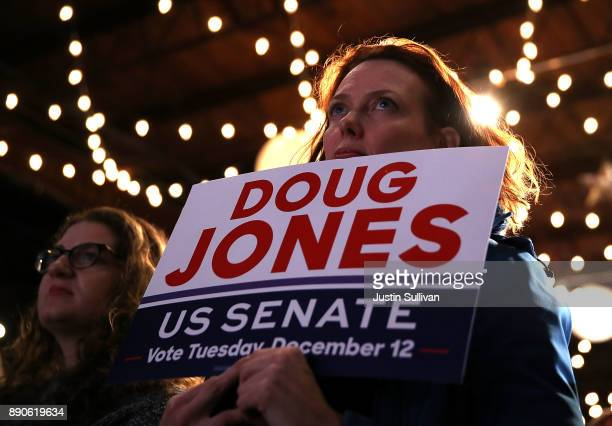 Supporters look on as democratic Senatorial candidate Doug Jones speaks during a get out the vote campaign rally on December 11 2017 in Birmingham...