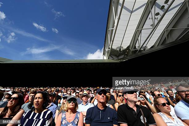Supporters look on in Centre Court on Middle Sunday of the Wimbledon Lawn Tennis Championships at the All England Lawn Tennis and Croquet Club on...