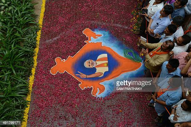 BJP supporters look on near a Rangoli decoration showing a portrait of Indian Bharatiya Janata Party prime ministerial candidate Narendra Modi with...