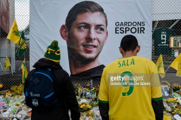 Supporters looks at flowers and messages left in front of a giant portrait of Nantes' Argentinian forward Emilianio Sala before the French L1...