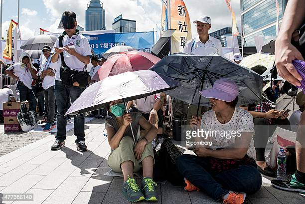 Supporters of a Chinabacked proposal to overhaul elections in Hong Kong sit under umbrellas outside the Legislative Council building in Hong Kong...