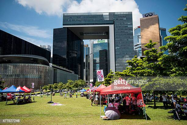 Supporters of a Chinabacked proposal to overhaul elections in Hong Kong sit under tents at Tamar Park near the Legislative Council building left and...