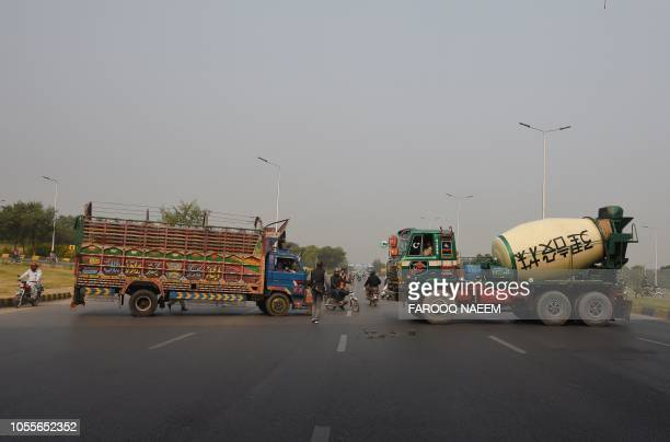 TOPSHOT Supporters of a Pakistani religious group block the Islamabad Highway with trucks after Supreme Court decision to overturn the conviction of...