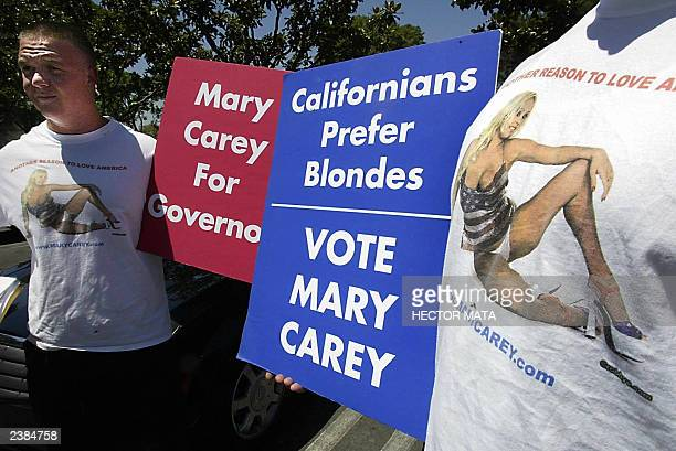 Supporters of adult film actress Mary Carey hold posters as she arrives at the Los Angeles County Registrar's Office in Norwalk CA to register her...