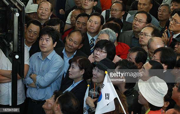 Supporters of Ahn Cheol Soo chairman of Ahnlab Inc look at a television screen as it broadcasts Ahn speaking during a news conference announcing his...