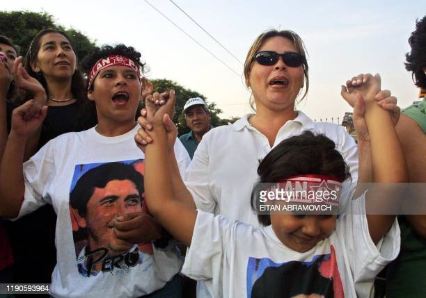 Supporters of Alan Garcia of the Apra party celebrate in Lima 08 April 2001 after the preliminary results of the elections were announced Garcia won...