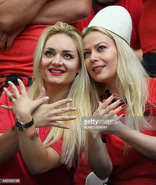 Supporters of Albania symbolize the Albanian flag with their hands as they cheer prior to the Euro 2016 group A football match between France and...