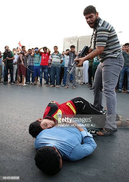 Supporters of alFadila party perform the simulation of an execution during a protest to ask for justice for members of the Iraqi forces who were...