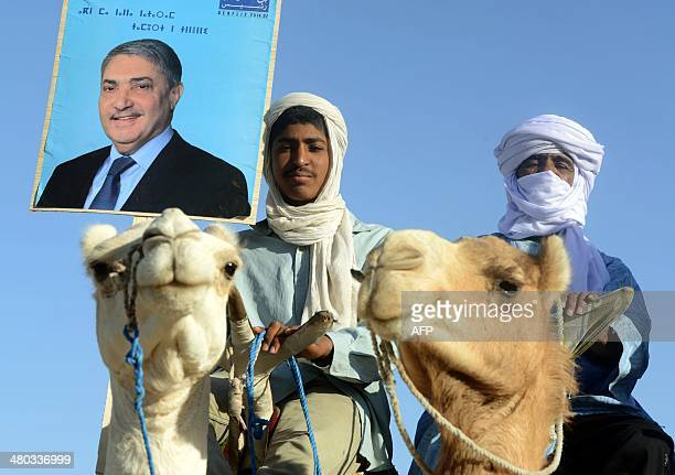 Supporters of Ali Benflis hold up his image as he arrives in to Adrar, 1 400 km southwest of the capital Algiers, as campaigning kicks off in Algeria...
