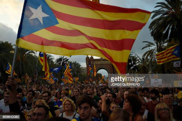 TOPSHOT Supporters of an independence for Catalonia listen to Catalan president Carles Puigdemont's speech broadcasted on a television screen at the...