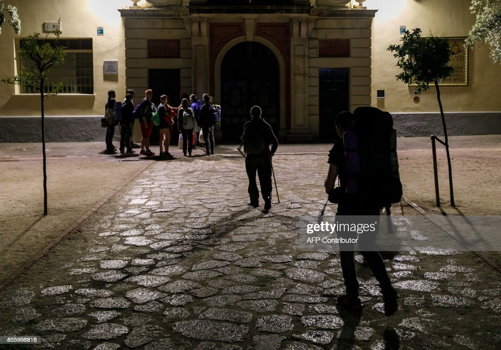 Supporters of an independence referendum in Catalonia arrive to spend the night at a designated polling station in a high school in Figueras in a bid to ensure the vote goes ahead, on September 30, 2017, on the eve of an independence vote that Madrid has banned and is trying hard to block. /