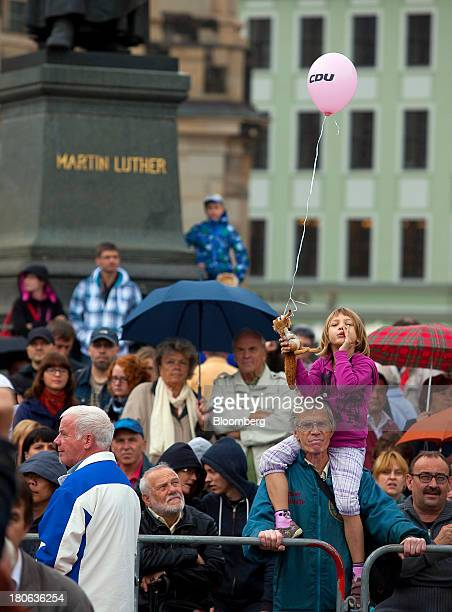 Supporters of Angela Merkel Germany's chancellor and party leader of the Christian Democratic Union wait for her to speak at an election rally in...