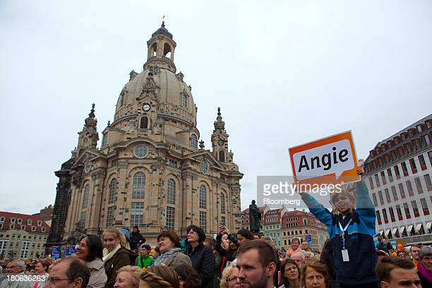 Supporters of Angela Merkel Germany's chancellor and party leader of the Christian Democratic Union stand at an election rally in Dresden Germany on...
