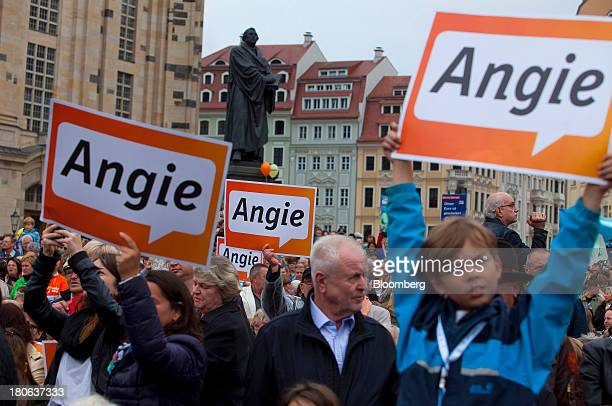 Supporters of Angela Merkel Germany's chancellor and party leader of the Christian Democratic Union hold signs while waiting for her to speak at an...