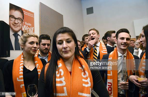 Supporters of Angela Merkel's CDU party react after state elections exit poll results are announced on tv an election party in Stuttgart southern...