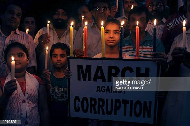 Supporters of anticorruption activist Anna Hazare hold placards and candles during a protest against corruption in Amritsar on August 23 2011 The...