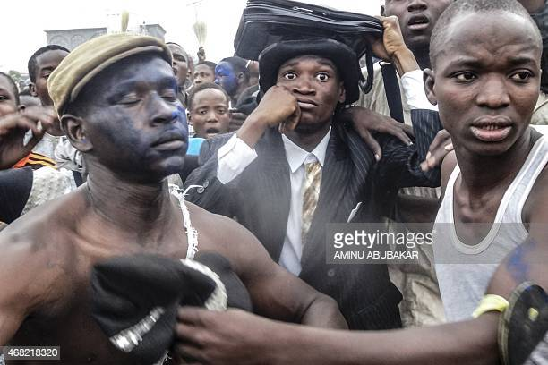 Supporters of APC surround a jester dressed as Nigeria's President Goodluck Jonathan as they celebrate the election victory of APC Presidential...