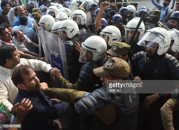 TOPSHOT Supporters of arrested opposition leader Shahbaz Sharif scuffle with policemen upon his arrival at a corruption court in Lahore on October 29...