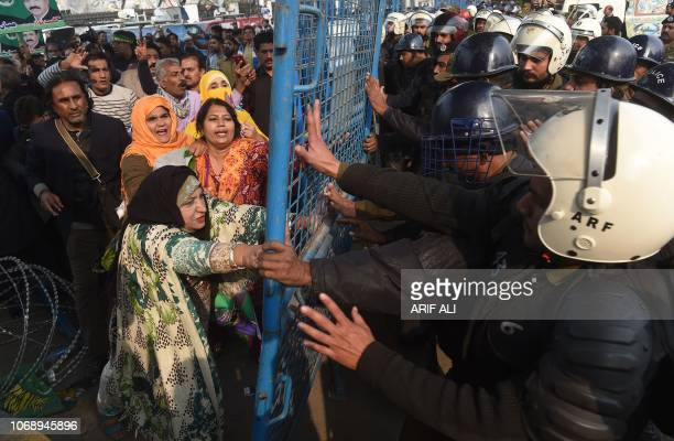 TOPSHOT Supporters of arrested opposition leader Shahbaz Sharif scuffle with policemen on his arrival at a corruption court in Lahore on December 6...
