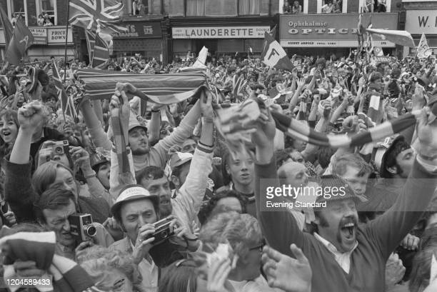 Supporters of Arsenal FC wave and cheer as they greet the team riding in an open top bus on a victory parade through the streets of Islington in...