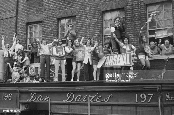 Supporters of Arsenal FC wave and cheer on a balcony in Upper Street as they greet the team riding in an open top bus on a victory parade through the...