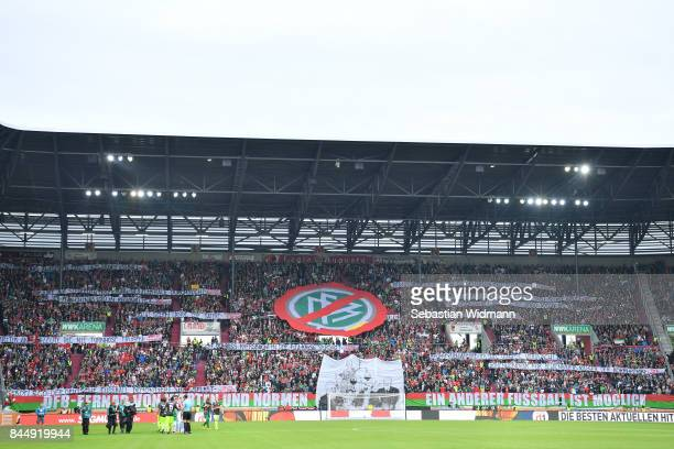 Supporters of Augsburg hold up a sign with a crossed out logo of the DFB during the Bundesliga match between FC Augsburg and 1 FC Koeln at WWKArena...