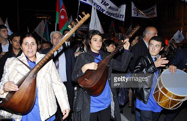 Supporters of Azerbaijani President Ilham Aliyev play music during a rally to show their support in central Baku on October 9 2013 as he was set to...