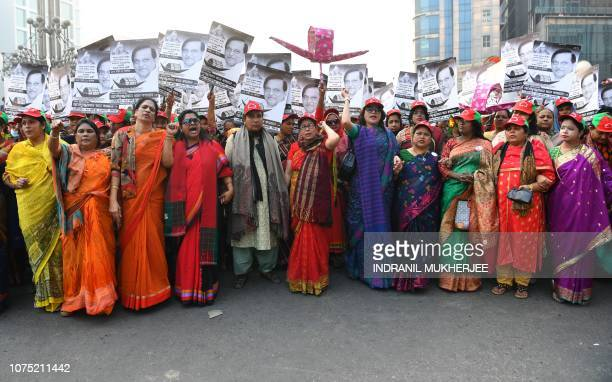 TOPSHOT Supporters of Bangladesh Awami League shout slogans while taking part in a rally ahead of December 30 general election vote in Dhaka on...