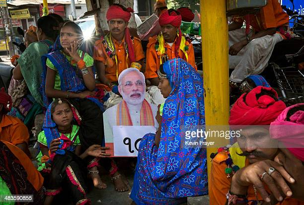 Supporters of Bharatiya Janata Party leader Narendra Modi sit near a placard showng his image after Modi filed his nomination papers on April 9 2014...