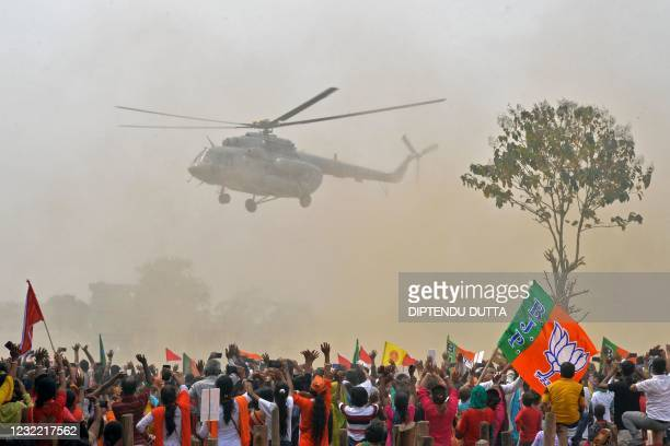Supporters of Bharatiya Janata Party wave towards a helicopter carrying Indian Prime Minister Narendra Modi upon his arrival at a public rally during...