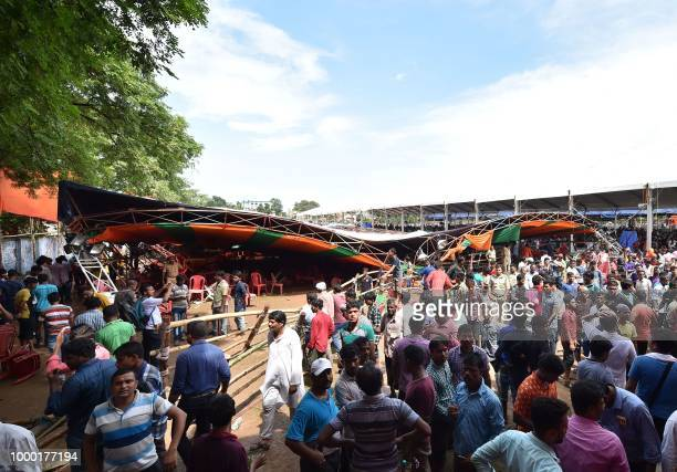 Supporters of Bhartiya Janta Party stand next to a damaged tent which collapsed during a public meeting addressed by India's Prime Minister Narendra...