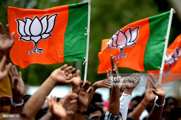 Supporters of Bhartiya Janta Party wave flags to their party president Amit Shah on his arrival at Chennai on July 9 2018 Shah arrived in Chennai on...