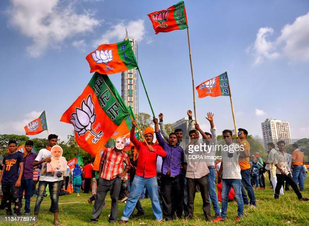Supporters of BJP seen waving Flags walking towards the meeting place of Brigade Parade Ground. Bharatiya Janata Party , the main ruling party of...