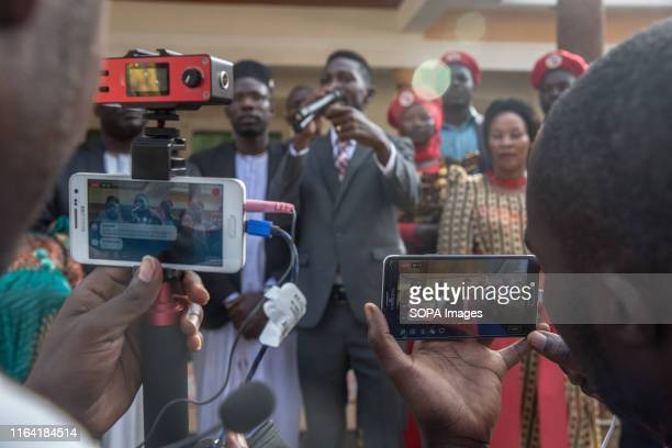 Supporters of Bobi Wine film his speech during a campaign event in Gombe Bobi Wine whose real name is Robert Kyagulanyi a popstar and opposition...