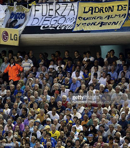 Supporters of Boca Juniors watch their Argentina First Division football match against Racing next to signs in support of Argentinian former player...