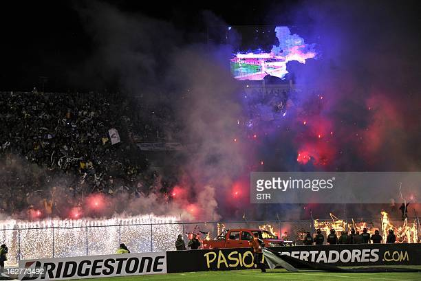Supporters of Bolivian San Jose light flares before the Libertadores Cup football match against Brazilian Corinthians in Oruro 240 km southeast from...
