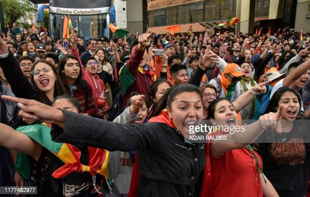 Supporters of Bolivia's main opposition presidential candidate, former president Carlos Mesa, shout slogans against supporters of president and...