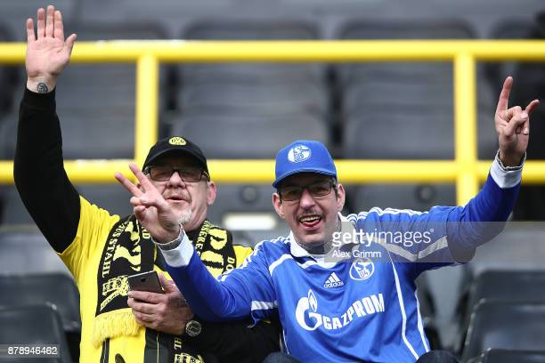 Supporters of both Schalke and Dortmund sit happily next to each other and wave and smile before the Bundesliga match between Borussia Dortmund and...