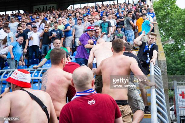 Supporters of both teams fight during the Third League Playoff Leg 2 match between SV Waldhof Mannheim and KFC Uerdingen at CarlBenzStadium on May 27...