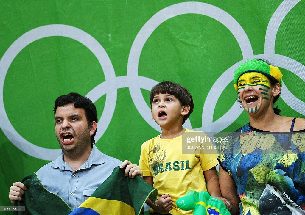 TOPSHOT - Supporters of Brazil cheer for their team during the women's qualifying volleyball match between Brazil and Argentina at the Maracanazinho stadium in Rio de Janeiro on August 8, 2016, during the 2016 Rio Olympics. / AFP / Johannes EISELE