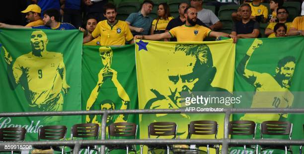 Supporters of Brazil display banners with images of Brazilian stars Ronaldo Cafu Tite and Neymar as they wait for the start of the 2018 World Cup...