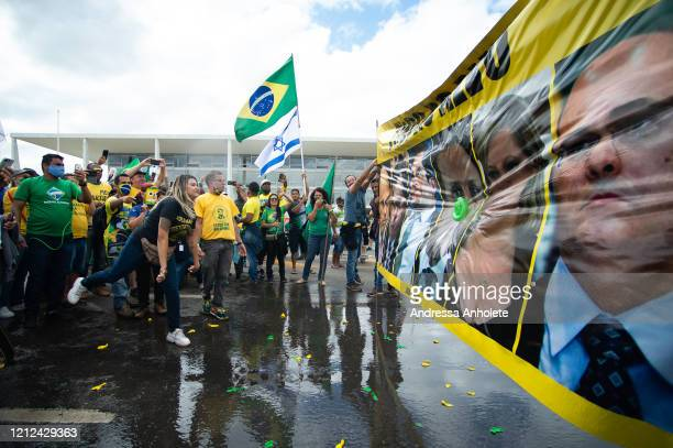 Supporters of Brazilian President Jair Bolsonaro throw water balloons at a banner with photos of Alexandre de Moraes, minister of Brazilian Supreme...