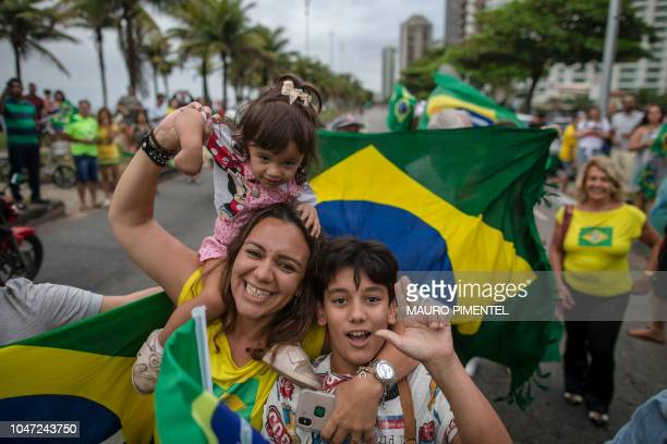 Supporters of Brazilian presidential candidate for the Social Liberal Party Jair Bolsonaro cheer in front of the residential condominium where he...
