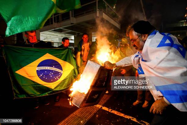 Supporters of Brazilian presidential candidate for the Social Liberal Party Jair Bolsonaro set on fire a model of an electronic voting device at...