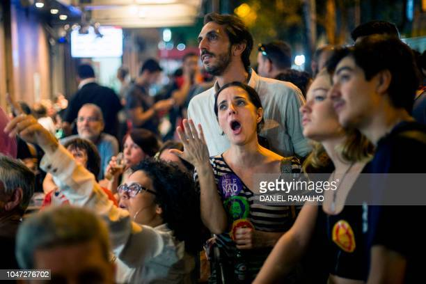 Supporters of Brazilian presidential candidate for the Workers' Party Fernando Haddad react during the general election vote count at a bar in Sao...